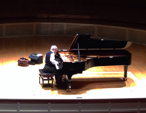 man playing grand piano in concert hall